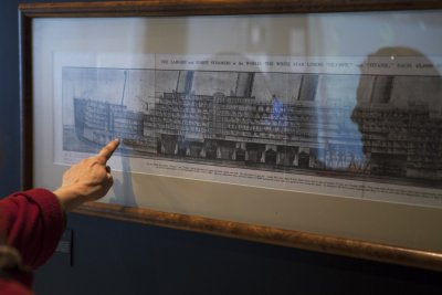 A patron points at a diagram showing the interior of the Titanic that hangs on the wall of an exhibit in the South Street Seaport Museum