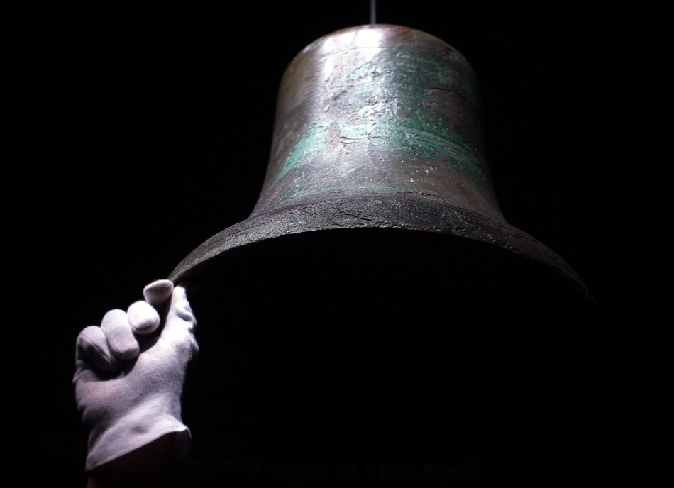 An exhibition worker holds steady the original ship's bell which rung out as the Titanic collided with an iceberg on her maiden voyage displayed as part of the 'Titanic:The Artefact Exhibition' at The Science Museum in London