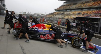 Red Bull Formula One driver Webber is pushed back to his garage during the second practice session of the Chinese F1 Grand Prix at Shanghai circuit