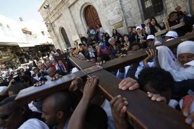 A Christian worshipper holds a cross as she takes part in the Eastern and Orthodox Churchs Good Friday procession in Jerusalem