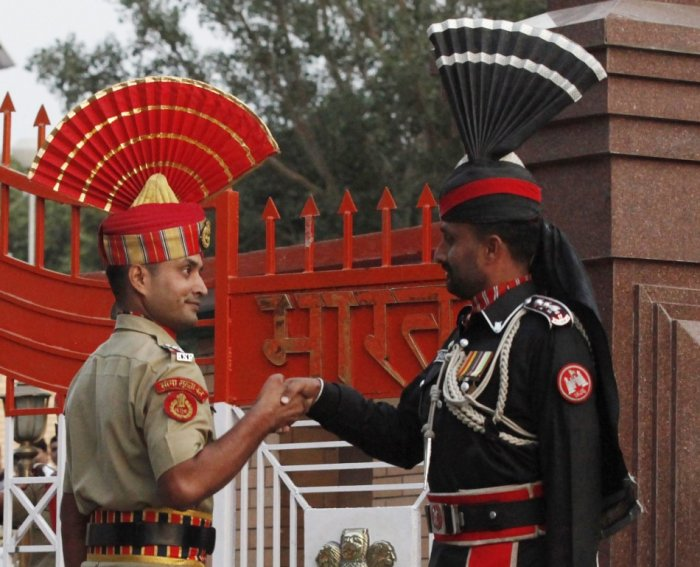 A Pakistani Ranger and an Indian Border Security Force officer shake hands during the daily parade at the Pakistan-India joint check-post at Wagah border