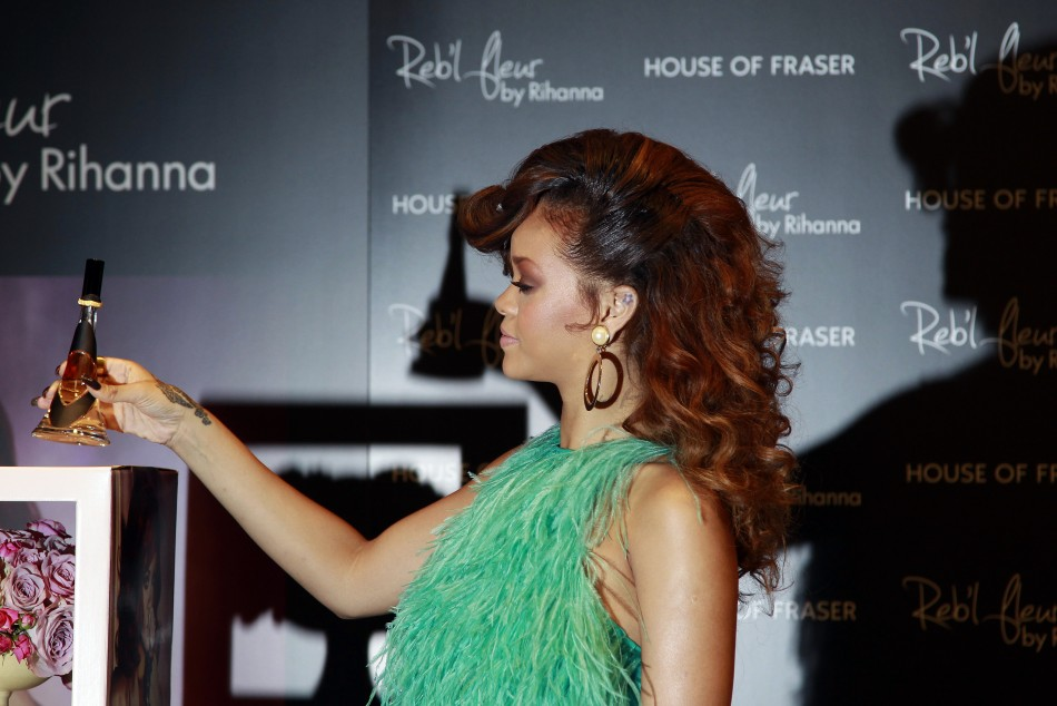 "Singer Rihanna holds a bottle of her fragrance ""Reb'l fleur"" at its launch at a House of Fraser department store on Oxford Street in London"