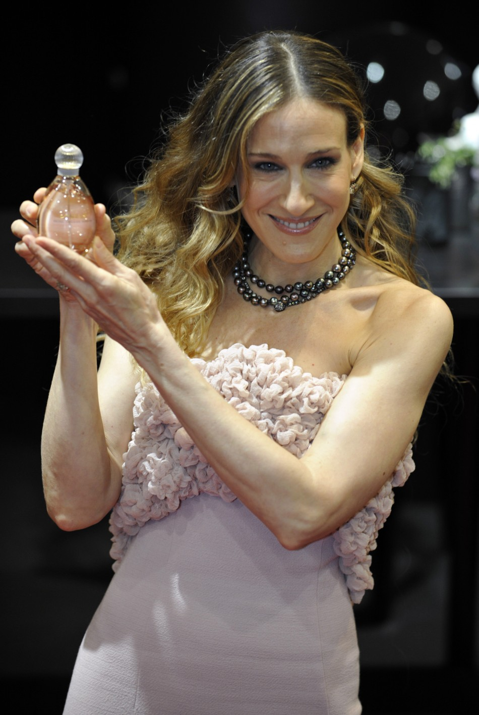 "US actress Sarah Parker holds a bottle of her perfume ""Lovely"" during a presentation in Paris"