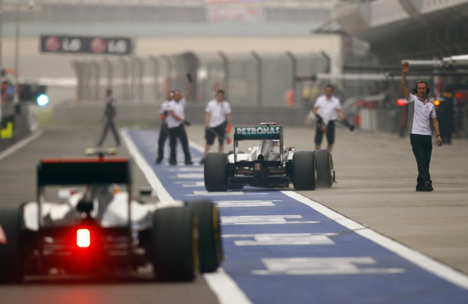 McLaren Formula One driver Hamilton and Mercedes039 Schumacher drive in the pit lane after the qualifying session of the Chinese F1 Grand Prix at Shanghai circuit