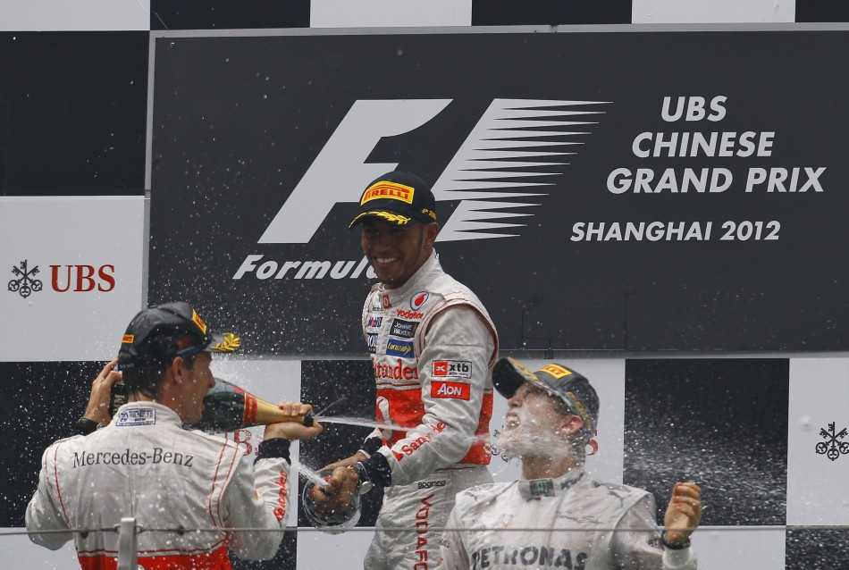 McLaren Formula One driver Button, team mate Hamilton and Mercedes039 Rosberg spray champagne at each other during the podium ceremony following the Chinese F1 Grand Prix at Shanghai circuit