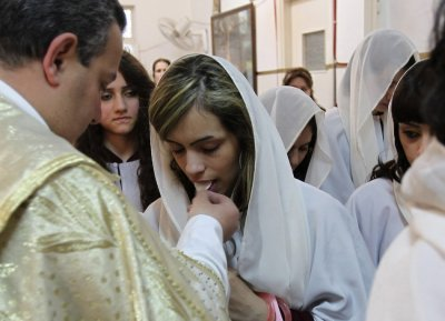 A priest gives communion to an Iraqi Christian during an Easter mass at Chaldean Catholic church in Amman