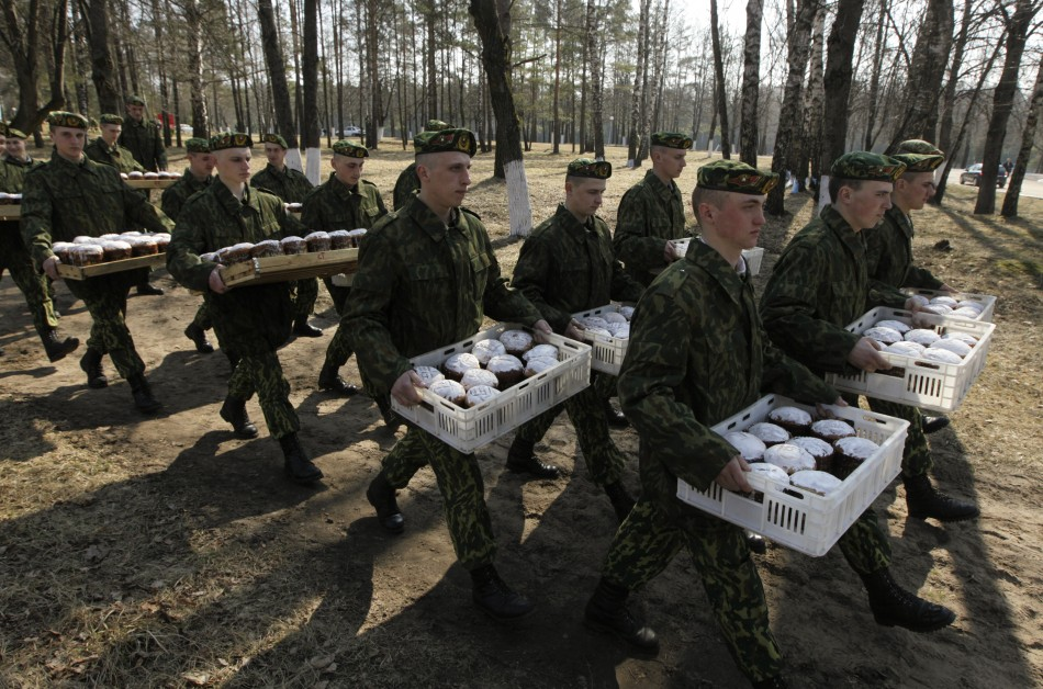 Belarussian Interior Ministry soldiers carry cakes after Orthodox Easter service at a military base near village of Okolitsa