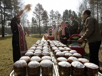 An Orthodox priest blesses Easter cakes during an Easter service at a military base near village of Okolitsa
