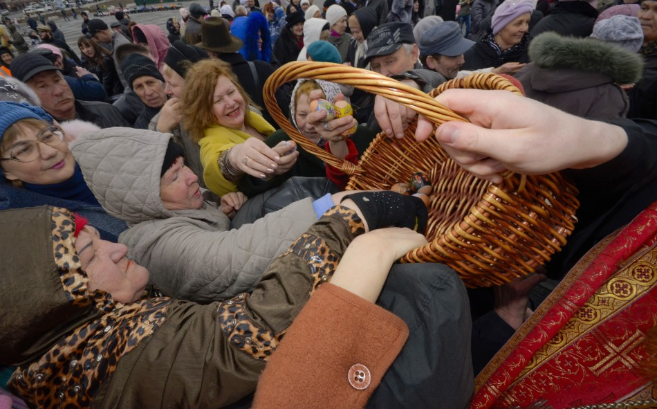 Worshippers take Easter eggs from a basket as they are distributed by an Orthodox priest after a religious service in Russia's far Eastern port of Vladivostok