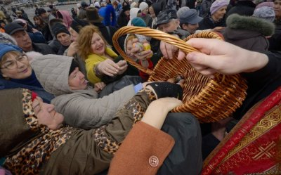 Worshippers take Easter eggs from a basket as they are distributed by an Orthodox priest after a religious service in Russias far Eastern port of Vladivostok