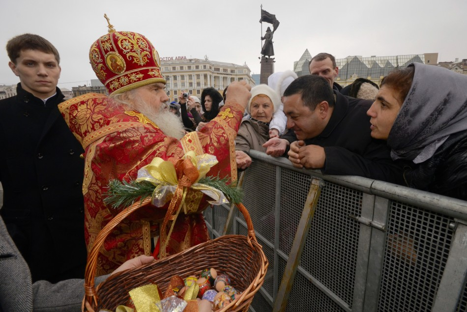 An Orthodox priest distributes Easter eggs to worshippers after a religious service in Russia's far Eastern port of Vladivostok