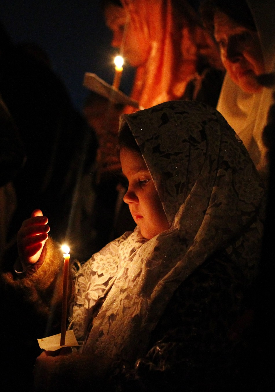 Russian Orthodox Old Believers hold candles during an Easter service at a church in Moscow