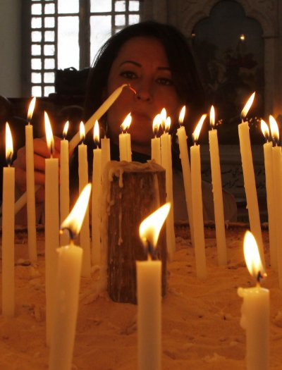 A woman lights a candle as she attends a mass of an Orthodox Easter at the Roman Orthodox patriarchate in Damascus