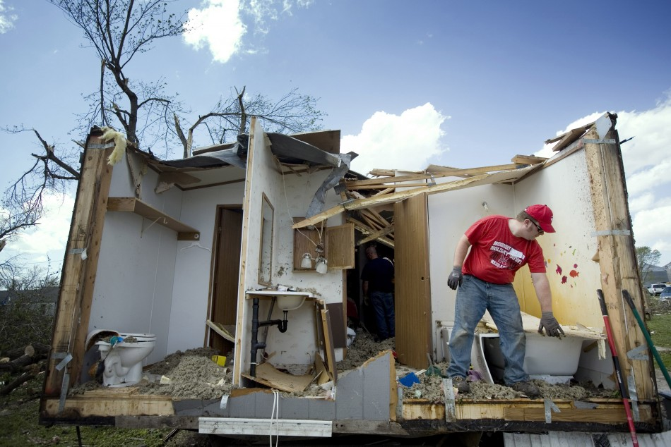 A man picks up debris from a damaged home in Thurman, Iowa