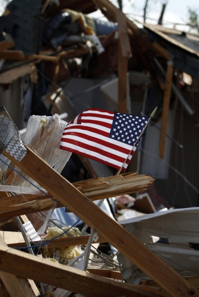 An American flag flies in the rubble of a home that was destroyed by a tornado in Woodward