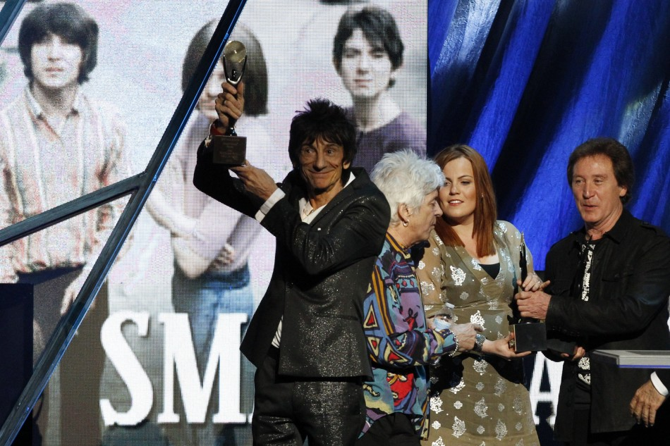 Ronnie Wood holds up the induction award as the band The Small Faces are inducted into the Rock n' Roll Hall of Fame in Cleveland, Ohio