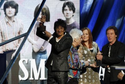 Ronnie Wood holds up the induction award as the band The Small Faces are inducted into the Rock n Roll Hall of Fame in Cleveland, Ohio