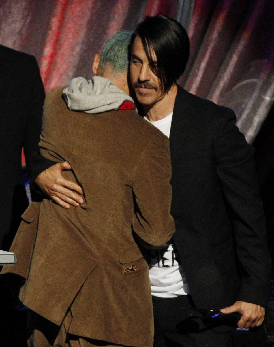 Lead singer Anthony Kiedis hugs band member Flea as the Red Hot Chili Peppers are inducted into the Rock n' Roll Hall of Fame in Cleveland, Ohio