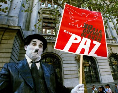 A mime impersonating actor Charlie Chaplin holds a peace sign during a protest in downtown Santiago