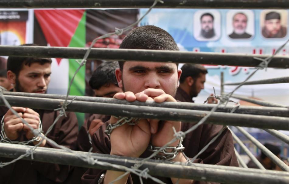 Hamas supporter portrays plight of Palestinian prisoners behind bars at rally in Jabalya, along northern Gaza Strip
