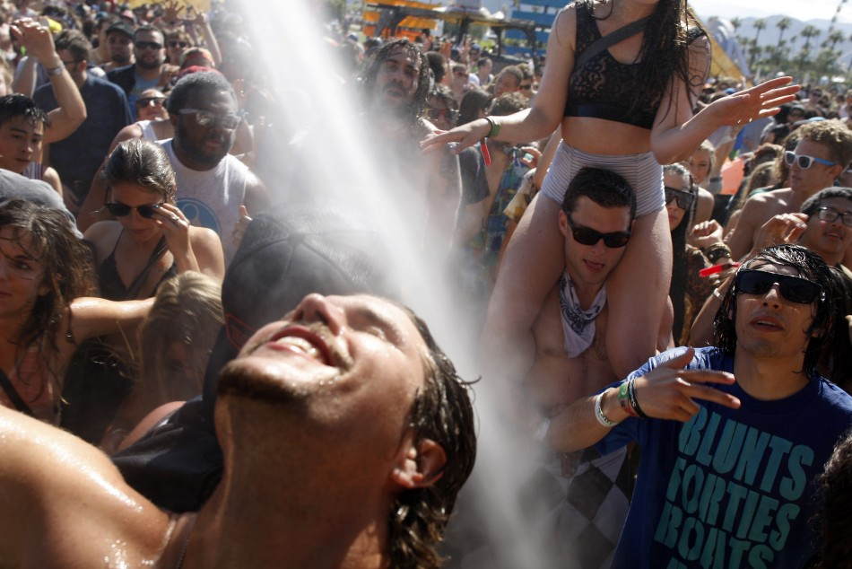 People dance under water sprayed from hoses at the Do Lab at the 2012 Coachella Valley Music and Arts Festival in Indio, California
