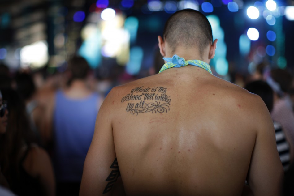 "A man with a tattoo that reads "" Music is the blood that unites us all"" dances as Flux Pavilion and Doctor P plays at the 2012 Coachella Valley Music and Arts Festival in Indio"