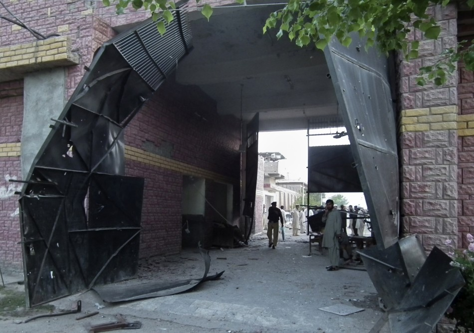 Policeman and security official stand near a damaged jail gate after inmates escaped from the prison in the town of Bannu