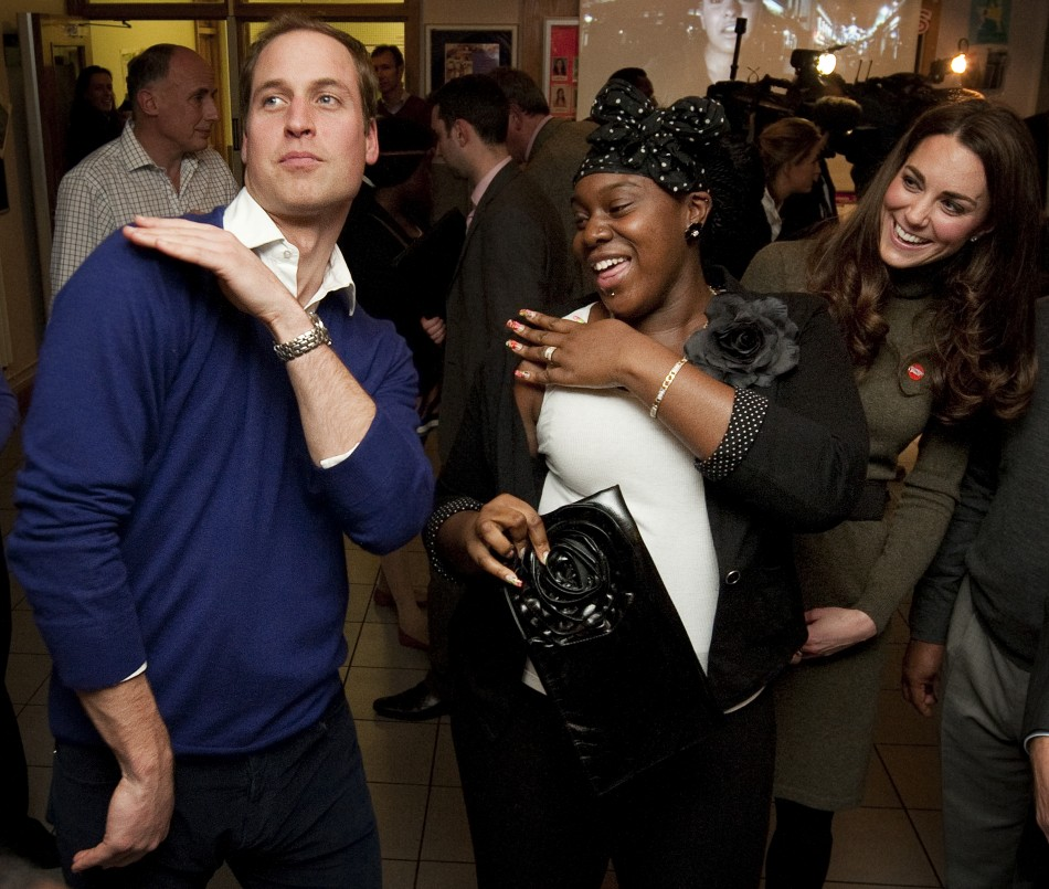 Britains Prince William dances with Vanessa Boateng as his wife Catherine, Duchess of Cambridge looks on during a reception at Centrepoints Camberwell Foyer in Londo