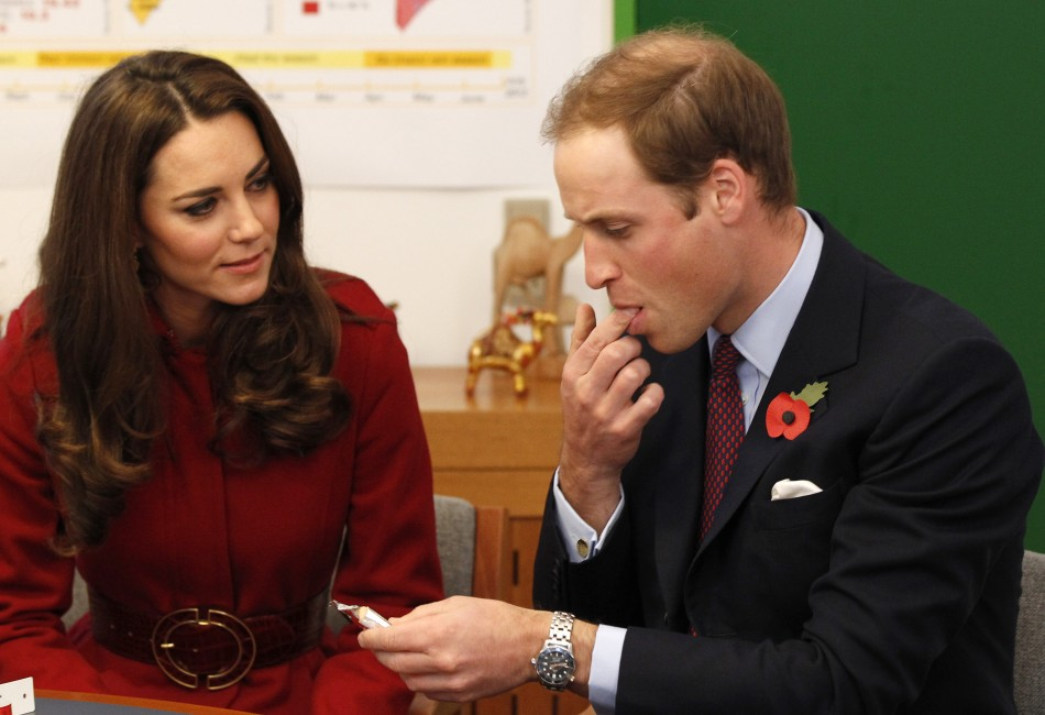 Britains Prince William watched by his wife Catherine, Duchess of Cambridge, tastes a high energy paste during a visit to the UNICEF emergency supply centre in Copenhagen, Denmark
