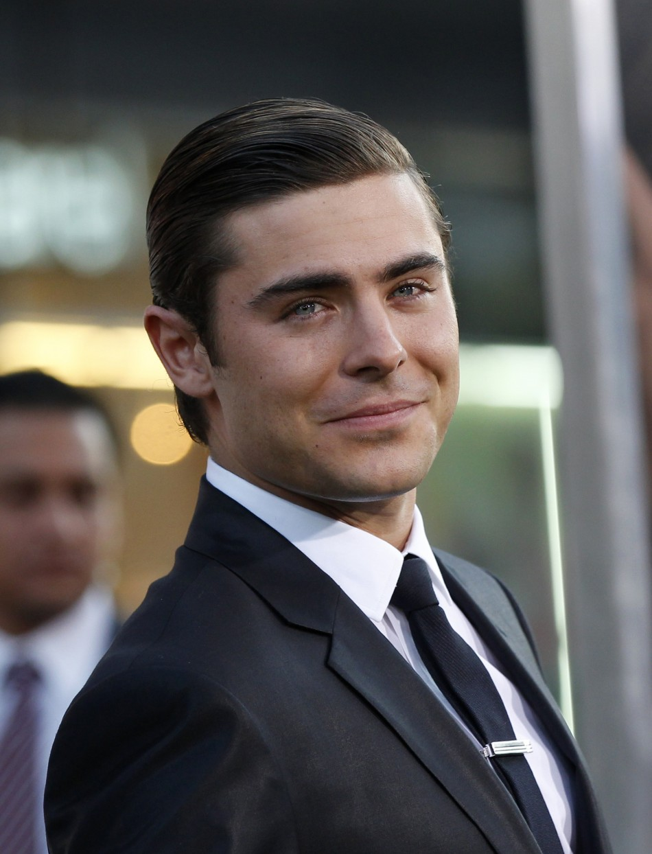 "Cast member Zac Efron drops a condom from his pocket when he poses at the premiere of ""The Lucky One"" at the Grauman's Chinese theatre in Hollywood, California April 16, 2012."