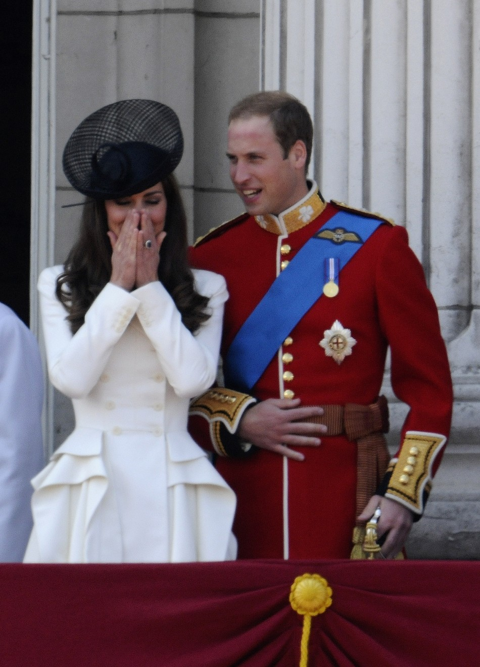 Britain039s Prince William and his wife Catherine, Duchess of Cambridge, share a light moment on the balcony of Buckingham Palace after attending the Trooping the Colour ceremony in central London