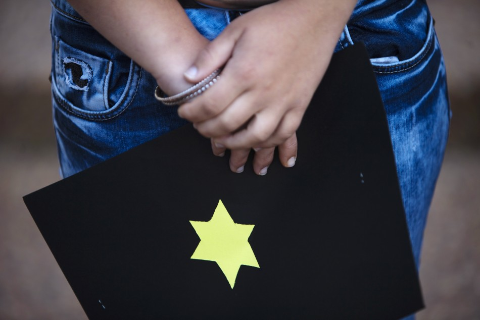 An Israeli holds a card with a yellow star of David outside the German Embassy in Tel Aviv during a demonstration against German author Guenter Grass after the sounding of a siren marking Israel's annual day of Holocaust remembrance April 19, 2012. Israel