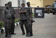 Prison officials wait outside the Lagos high court where Hamza Al-Mustapha is standing trial