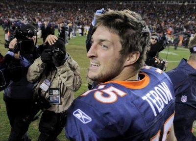 Denver Broncos quarterback Tim Tebow celebrates after his team defeated the Pittsburgh Steelers in overtime in the NFL AFC wildcard playoff football game in Denver