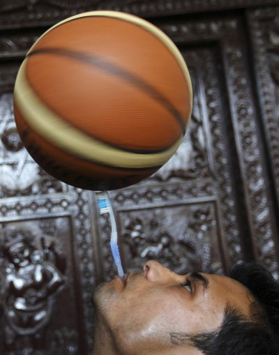Thaneshwar Guragai spins a basketball on a toothbrush while holding the toothbrush in his mouth for exactly 22.41 seconds to break the last Guinness record of 13.5 seconds set by Thomas Connors of U.K, in Kathmandu