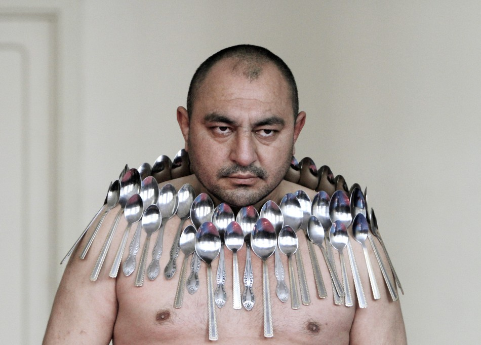 "Etibar Elchiyev poses with 50 metal spoons magnetized to his body during an attempt to break the Guinness World Record for ""Most spoons on a human body"" in Tbilisi"