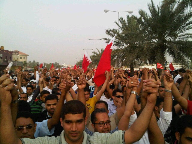 Shias and Sunni protesters hold hands as they reject claim their protests are based on sectarian demands