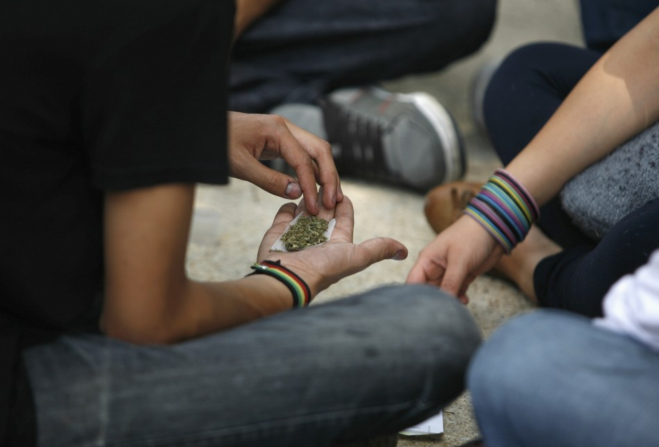 Man holds shredded marijuana in the palm of his hand during rally to demand the legalization of marijuana in Mexico City