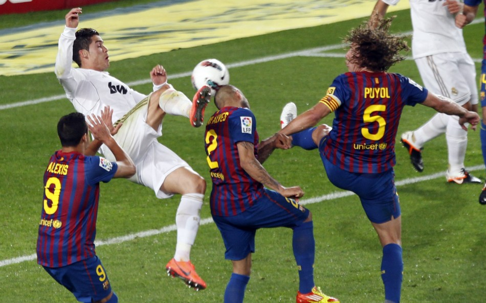 Real Madrid039s Ronaldo kicks the ball surrounded by Barcelona039s Alexis, Alves and Puyol during their Spanish first division quotEl Clasicoquot soccer match in Barcelona