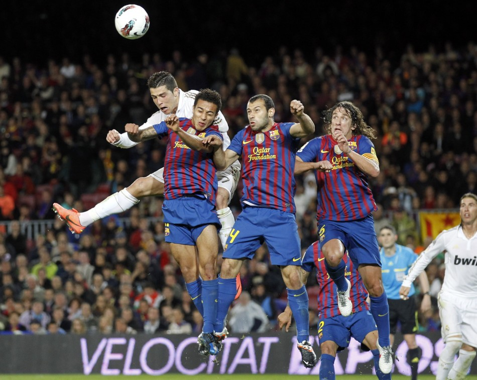 Real Madrid039s Ronaldo heads the ball surrounded by Barcelona039s Thiago, Mascherano and Puyol during their Spanish first division quotEl Clasicoquot soccer match in Barcelona