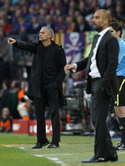 Real Madrid039s coach Mourinho gestures next to Barcelona039s cocah Guardiola during their Spanish first division soccer match in Barcelona