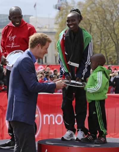 Prince Harry L presents a trophy to Gerard R, the son of Kenya039s Mary Keitany