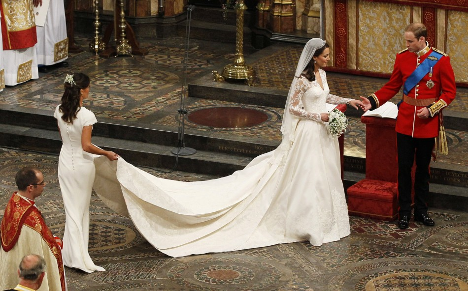 Maid of Honour, Pippa Middleton L holds the wedding dress of her sister Catherine, Duchess of Cambridge, after her she married Britain039s Prince William at Westminster Abbey, in central London