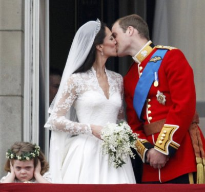 Britains Prince William and his wife Catherine kiss as they stand next to bridesmaid Grace van Cutsem in central London