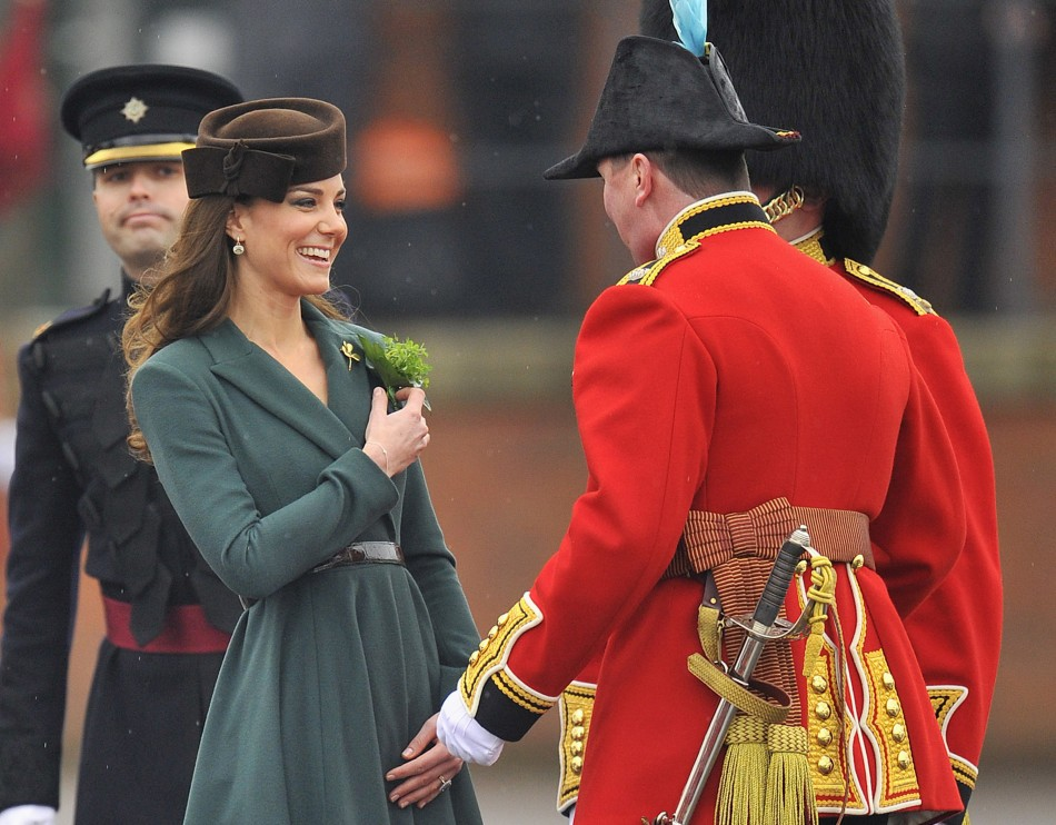 Britain's Catherine, Duchess of Cambridge, presents shamrock flowers to members of 1st Battalion Irish Guards at parade ground at Aldershot army base in southern England