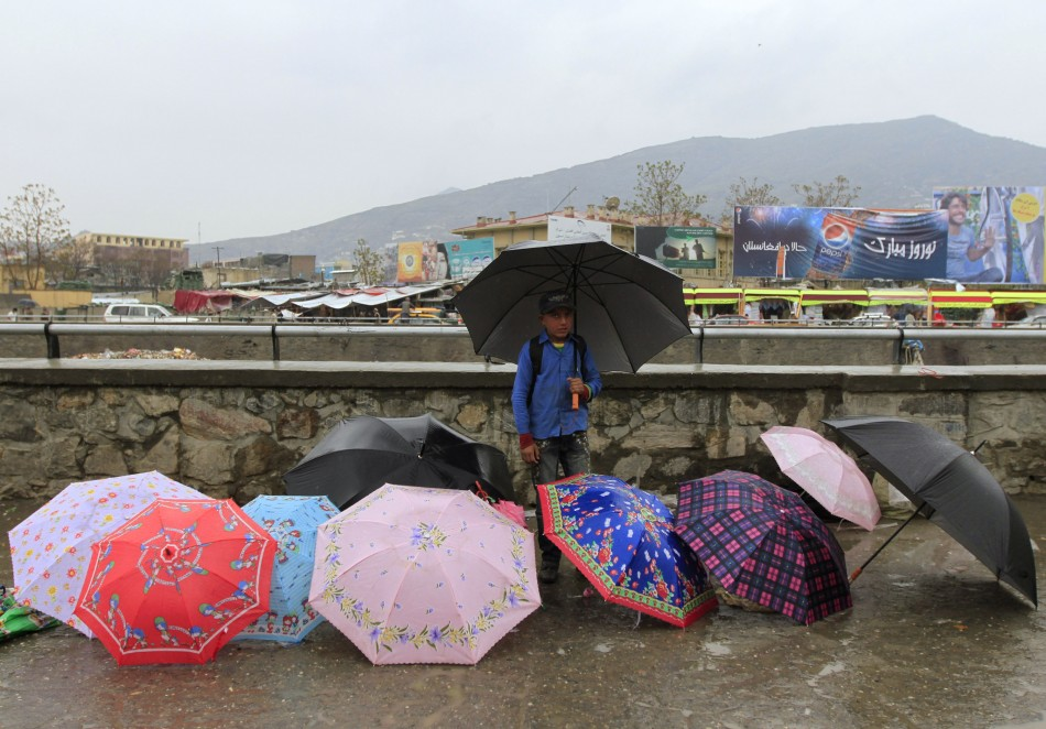 A boy sells umbrellas along a river in Kabul April 19, 2012.