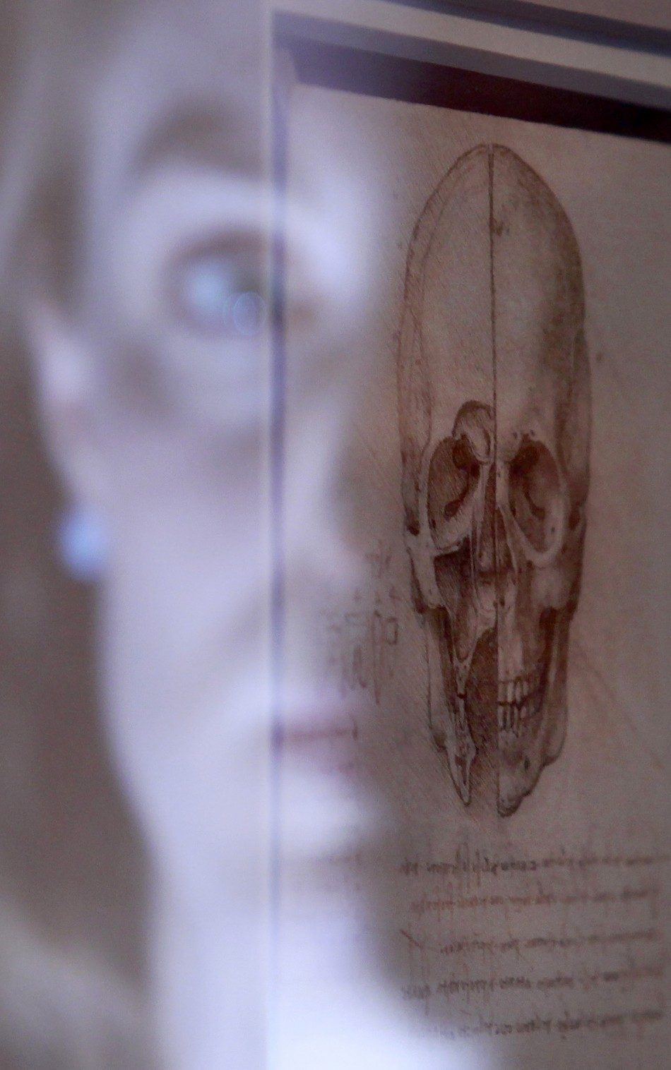 Employee Alice Ross reflection is illuminated as she poses with artist Leonardo da Vinci039s drawing quotA skull sectioned, 1489quot at the Queen039s Gallery at Buckingham Palace in London