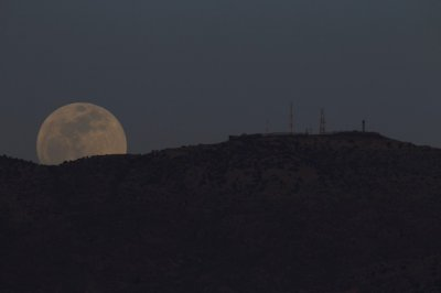 The full moon rises from the top of the Haramoun mountain