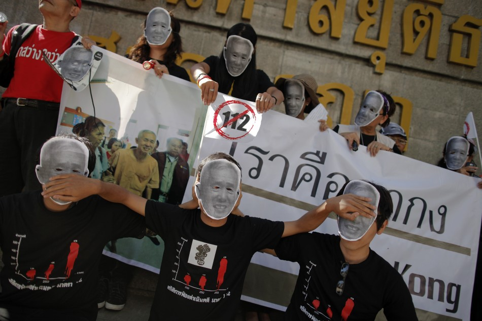 Protesters against Thailand's lese-majeste laws wear masks and hold pictures of Amphon Tangnoppaku, who has died during whole serving a 20-year sentence for defaming the Queen (Reuters)