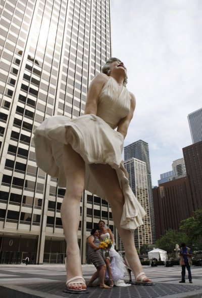 A newly wed bride and her maid of honor pose beneath a 26-foot tall statue of Marilyn Monroe in Chicago